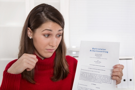 Young disappointed woman staring at business contract in german language - time work