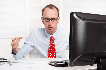Businessman with bald and glasses aggressive and in rage sitting at office with computer. photo