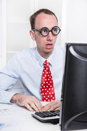 Shocked businessman at desk staring at computer and cant believe it - problems at work. photo