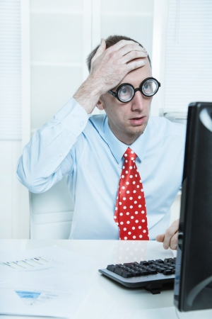 Businessman with a red tie and a blue shirt has made a mistake - touching his head at desk looking in his computer. photo