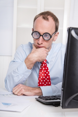 Overworked businessman with glasses staring into space at desk - stress and burnout - everyday life at the office