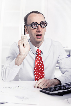 Slimme jonge zakenman met kale hebben een oplossing te werken als wetenschapper met grote glazen - grappig concept voor een workaholic of een vrek.