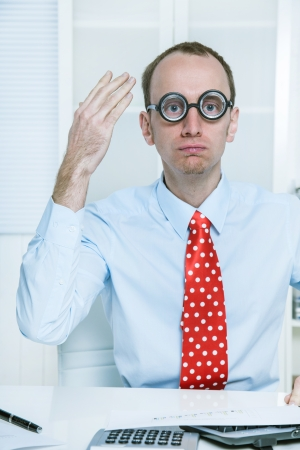 miserly: Stunned man with big glasses and a red tie at work like a comedian, bookkeeper or manager with good ideas - hands up.