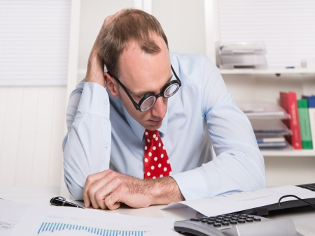 finance director: Frustrated businessman wearing glasses sitting at desk with head in hands isolated on white background - no success