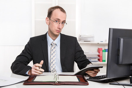 examiner: Typical examiner or controller - arrogant and disagreeable sitting at desk with his computer and business numbers.  Stock Photo