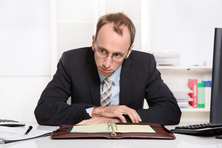 demotivated: Businessman at desk with problems, stress and overworked sitting in his office - burnout