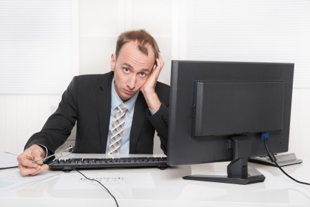 demotivated: Frustrated employee sitting and desk holding his head - headache or migraine.