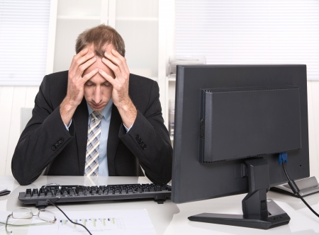 finance director: Overworked businessman frustrated and stressed in his office with computer - headache. Stock Photo