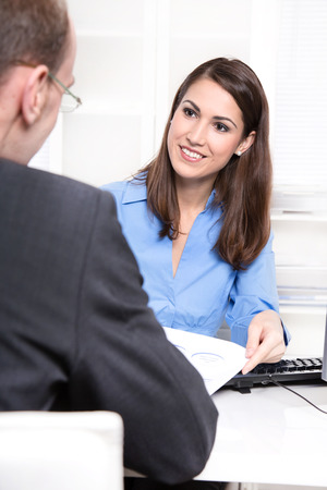 Happy businesswoman in a blue blouse in interview or meeting with a man also as consultant for a insurance.  photo