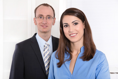 Portrait of a successful business team - he in suit and tie and she smiling in a blue blouse - teamwork photo