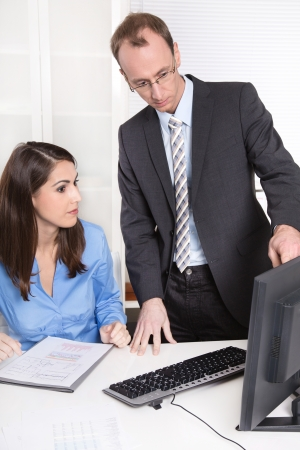 Successful businessman with suit and tie explain something his secretary in a blue blouse sitting at desk - teamwork.