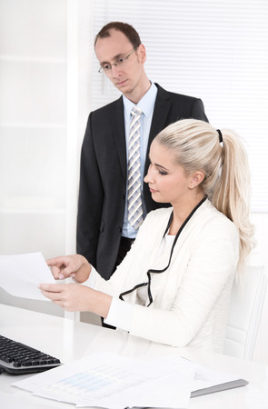 hair tie: Successful businessman with suit and tie talking with his blond beautiful secretary in a white clothes - fashion.