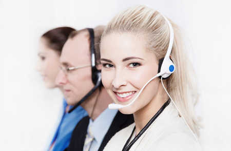 helpful: Telesales or helpdesk team - helpful blonde beautiful woman with headset smling at camera