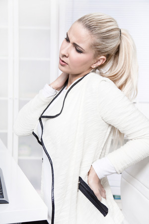 pains: Young beautiful business woman has pains on her back - disc herniation - lack of exercise or not ergonomic work place. Stock Photo