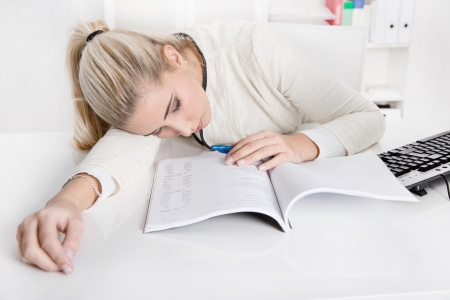 disconsolate: Blonde overworked businesswoman or trainee sleeping at desk over business papers during work time.