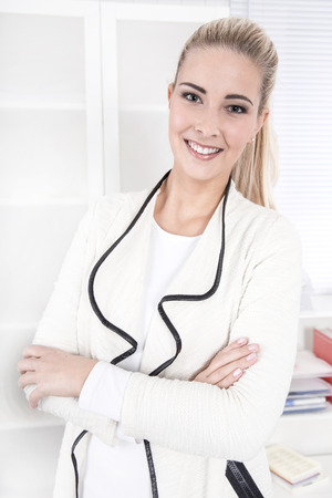 Portrait of a young blonde smiling businesswoman arms folded isolated on white - photo for application photo