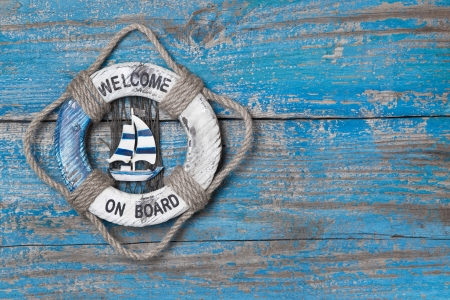 Welcome on board - lifebuoy blue wooden background Stock Photo