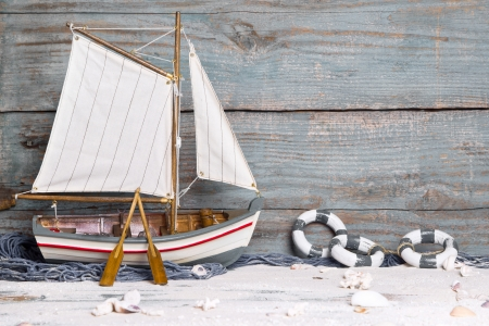 Sailboat or fishing boat made of wood as nautical decoration on wooden background photo