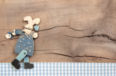 accessorize: Easter decoration with a blue bunny on a wooden background in shabby chic style with a blue checked frame for greeting card.