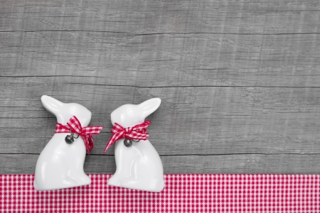 accessorize: Easter rabbits decoration in interior on a wooden background in red and white chequered for greeting card.