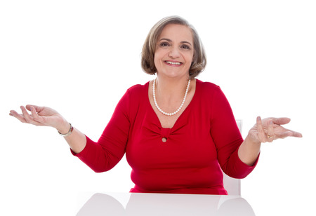 outstretching: Puzzled senior woman sitting in office isolated on white