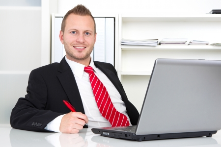 Business manager in office sitting with laptop and pen in hand photo