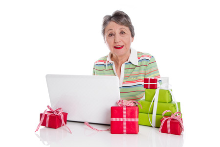 Grandmother ordered online gifts. Senior lady with presents and laptop. Stock Photo - 23827274