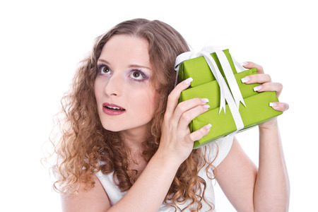 frenetic: Girl isolated hears what the green gift box is inside. Stock Photo
