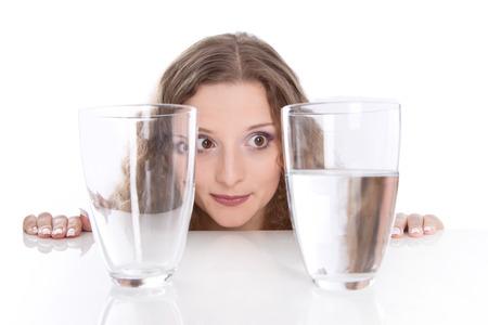 actitud positiva: ¿Medio vacío - lleno a la mitad. Concepto - Todo es cuestión de opinión. Mujer joven con dos vaso de agua, aislado en blanco Foto de archivo