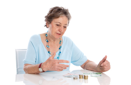 scarce:  Pensioner counts her income - pension scarce Stock Photo