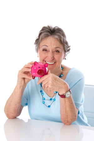 gray haired:  Pensioner - woman isolated pleased with their savings. Mature lady with piggy bank.