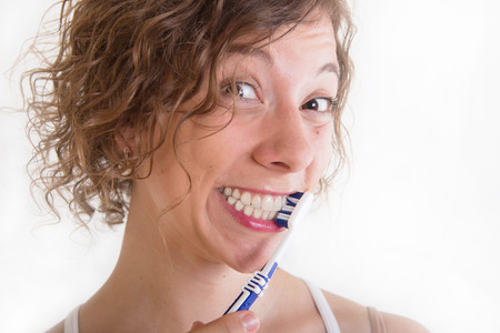 Funny woman brushing teeth isolated on white Stock Photo - 23797370