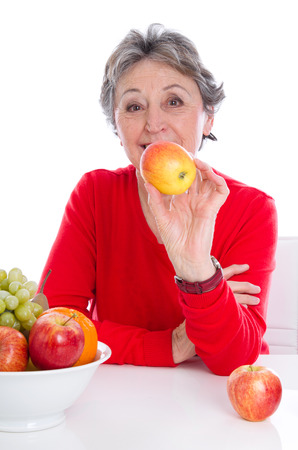 gray haired: Balanced diet - gray haired senior woman with fruits isolated Stock Photo