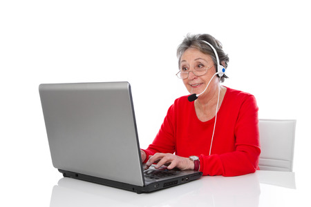Mature woman with headset isolated in red with computer photo