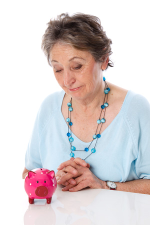 savings problems: Poverty in old age - woman looks down sadly at her savings, piggy bank Stock Photo
