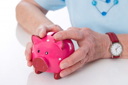Pensioner holding her piggy bank firmly in the hands photo