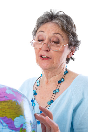 70 75: Senior goes on a journey - elderly woman with globe isolated Stock Photo