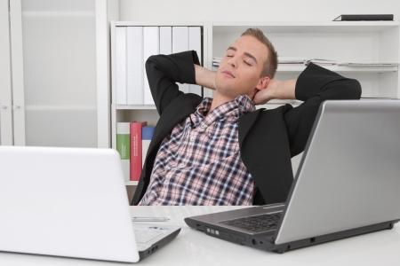 cansancio: El hombre tranquilo - Daydreams en la oficina entre las computadoras portátiles