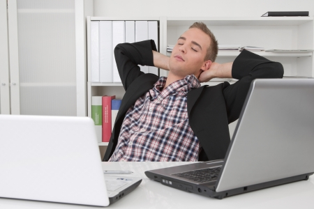 between: Relaxed man - Daydreams in the office between laptops