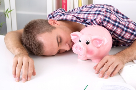 thrift box: Pay tuition fees from the piggy bank. Tired young student laying on desk with savings.