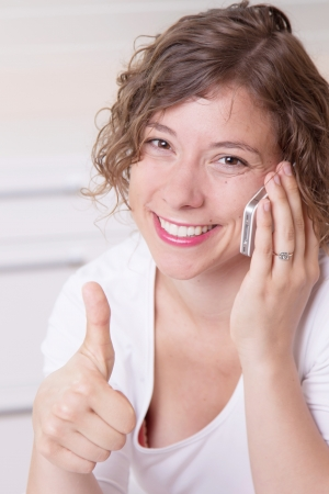 Happy woman on phone with thumbs up in office Stock Photo - 23837021