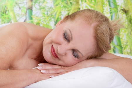 Senior lady with closed eyes relaxing in massage photo