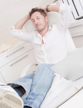lunchbreak:  Man relaxing in the office, putting his legs on table Stock Photo