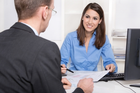 client meeting: Saleswoman: Businesswoman sales an insurance or makes finance at desk - supporting a customer.