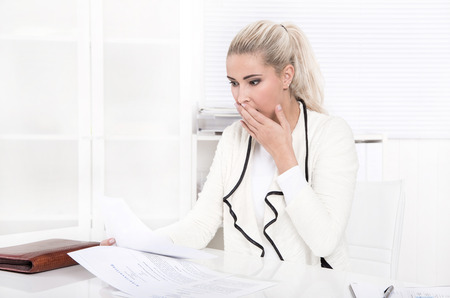 cancellation: Shocked blonde businesswoman at desk - looking at income and outgoings.