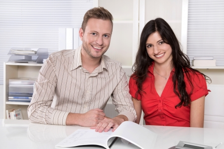 takes: Young couple sitting in a meeting - holding hands - making investment or takes a credit.