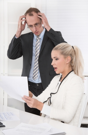 outgoings: Shocked and frustrated manager with his secretary looking at balance sheet.