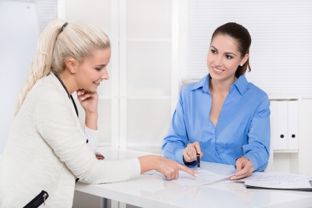 Two beautiful woman at desk - financial business meeting or recruitment. photo