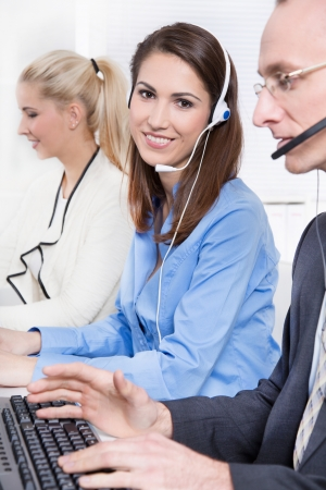 customer facing: Agent smiling while working in a call-center - with head-set.