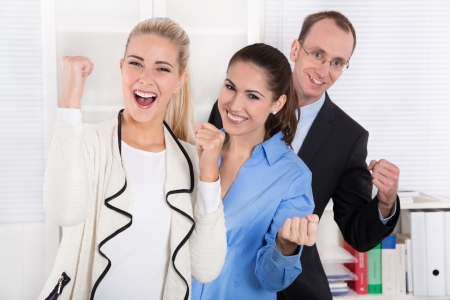 thumps up: Happy business team - young man and woman - work colleagues celebrating success.